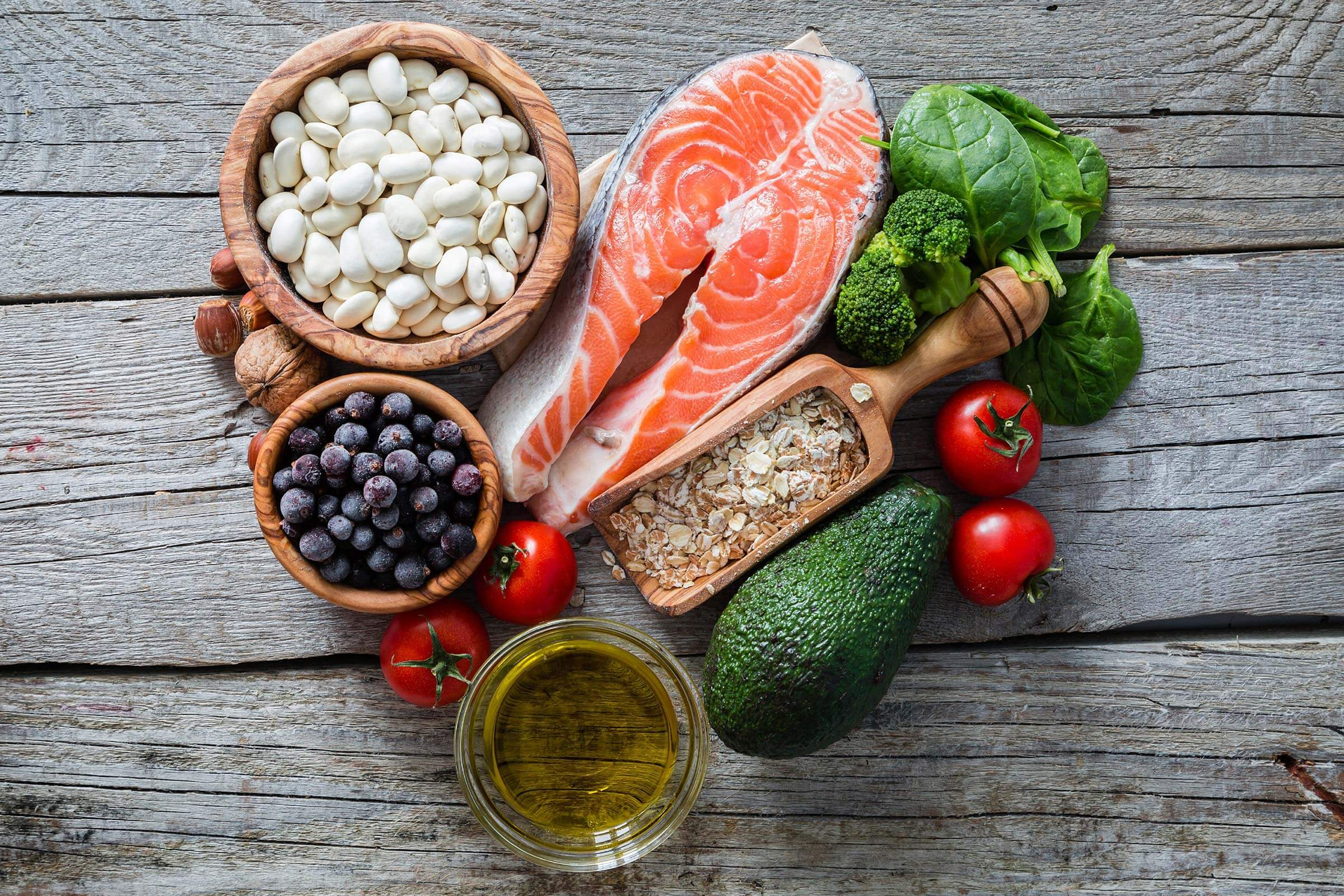 A photo of healthy fats including blueberries, tomatoes, avocado, and beans.