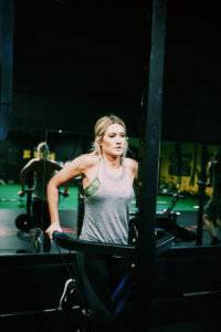 A woman uses workout equipment with a mirror behind her.