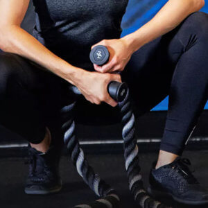Photo of woman holding battle ropes in a squatting position.