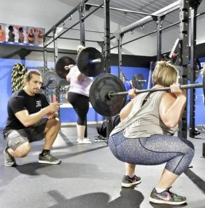 A woman performs a squat at the bar under the supervision of an Elite Edge coach.