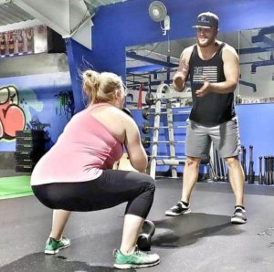 A woman squats in preparation to throw a medicine ball to her trainer.