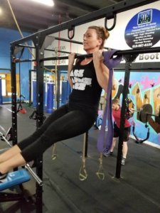 A woman does a pull up at Elite Edge.