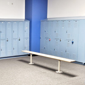 A photo of blue lockers and a bench in an Elite Edge locker room.