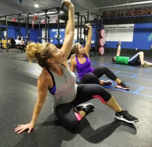 A photo of three people working out at Elite Edge utilizing kettlebells.
